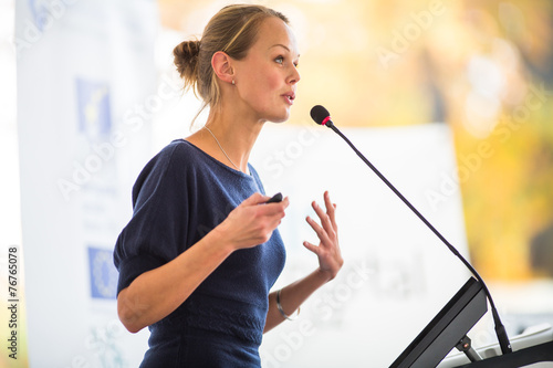 Pretty, young business woman giving a presentation - 76765078