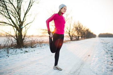 Young woman stretching while running outdoors on a cold winter