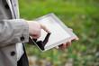 Men using digital tablet PC in the park.