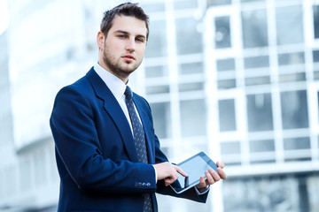 Businessman using a digital tablet computer, standing in front o
