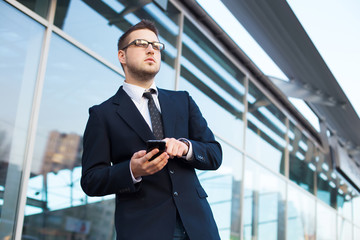 Attractive young businessman using a cell phone.