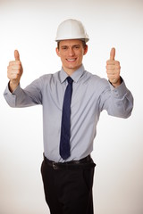 Young businessman in a protective helmet shows you thumbs up