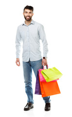 Handsome man holding shopping bags on white background