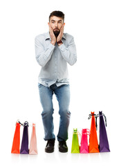 Handsome man with shopping bags is shocked on white background