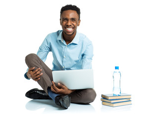 Happy african american college student sitting with laptop on wh