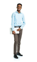 Happy african american college student standing with laptop on w