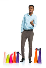 Happy african american man with shopping bags  and holding credi