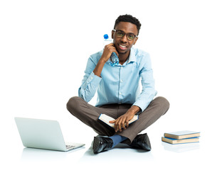 Happy african american college student sitting with laptop, book