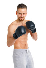 Athletic attractive man wearing boxing gloves on the white