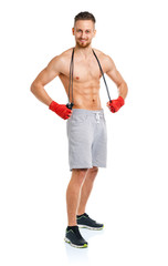 Athletic attractive man jumping on a rope on the white