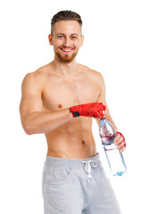 Athletic attractive man wearing boxing bandages with bottle of w