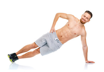 Athletic attractive man doing fitness exercises on the white