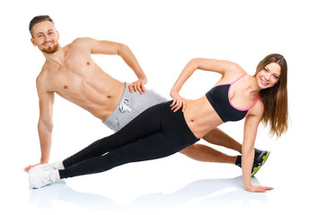 Athletic attractive couple - man and woman doing fitness exercis