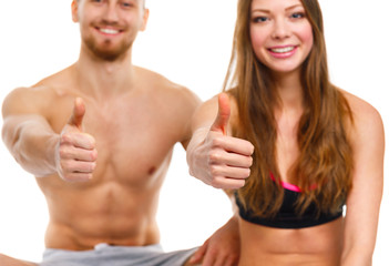 Athletic man and woman after fitness exercise with a finger up o