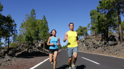 Running couple jogging on road healthy lifestyle