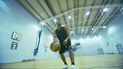 Mixed race basketball player dribbling the ball up the court