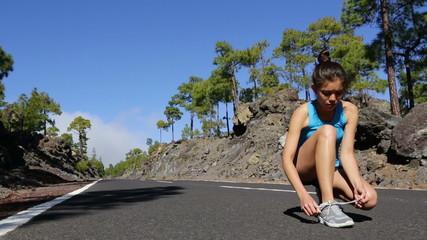 Young woman tying running shoes before run