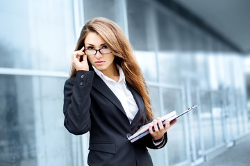 Successful businesswoman taking notes and talking on cellphone