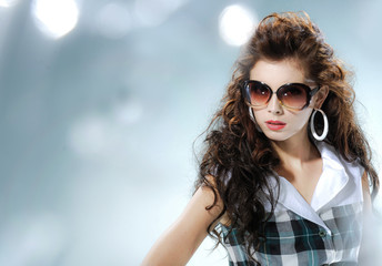 fashion shot of girl with sunglasses posing in light background