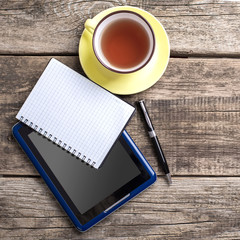 Workspace with coffee cup, tablet pc on old wooden table