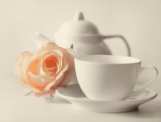Delicate roses beside a white cup