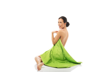Side view woman sitting wrapped in towel