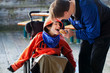 Father feeding disabled son a hamburger in wheelchair. Child has - 76779450
