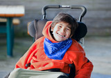Handsome, happy biracial eight year old boy smiling in wheelchai - Fine Art prints
