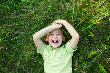 laughing little boy on the grass