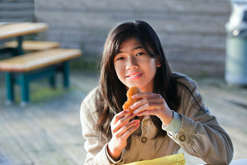 Young biracial teen girl outdoors eating hamburger