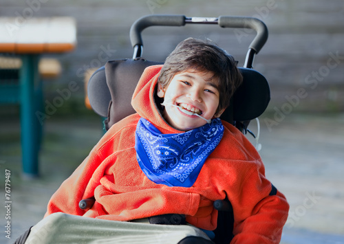 Handsome, happy biracial eight year old boy smiling in wheelchai - 76779487