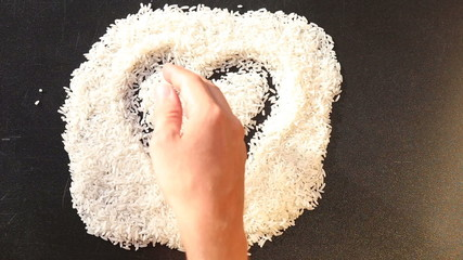 man hand is drawing a heart on white rice