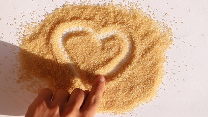 man hand draw heart on surface of sugar and put his hand on it a