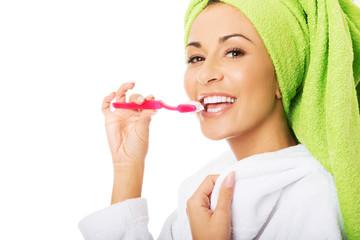 Portrait of a woman in bathrobe brushing teeth