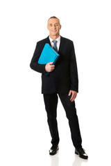 Full length mature businessman holding a binder