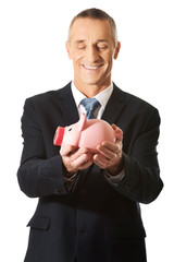 Portrait of cheerful businessman holding piggybank