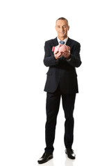 Happy businessman holding piggybank