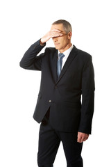 Stressed businessman covering his face