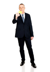 Full length businessman showing a yellow card