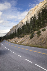 Mountain road under majestic rocky cliffs