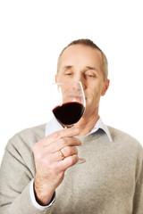 Mature man tasting red wine