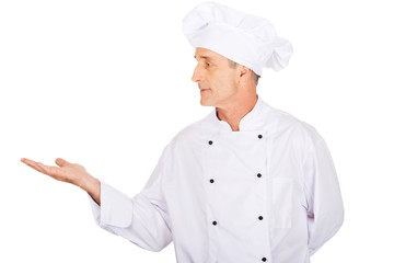 Mature chef showing copyspace on the left
