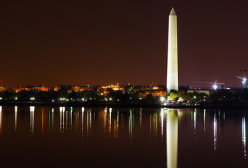 Washington Monument at night and city skyline on background