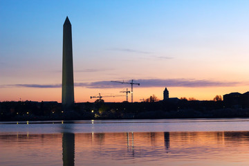Washington Monument at dawn and city skyline on background.