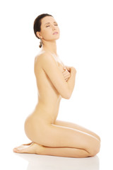 Nude woman covering her breast