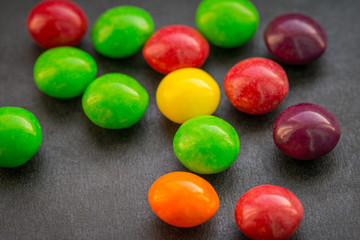 Colorful chewy dragees on a dark background.