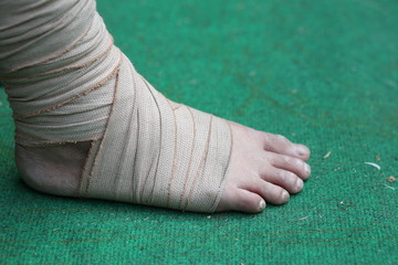 Foot and Ankle injured with bandage on green background