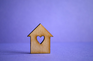 Wooden house with a hole in the form of heart on a purple backgr