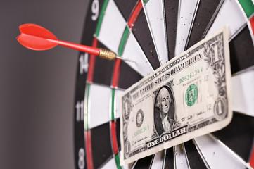 One dollar bill on a dartboard.