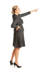 Businesswoman pointing high on copyspace